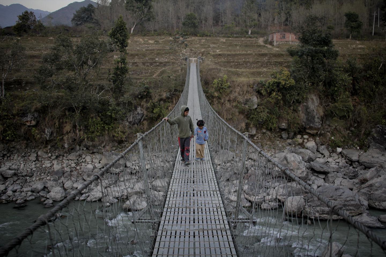 Binu Dangol,4, and Bishal Dangol, 12 walks through a bridge in Trishuli.