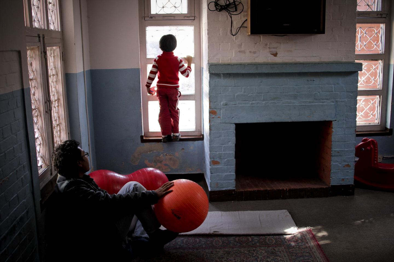 Kreet Amatya looks outside the window for his mother Dr Sunita.